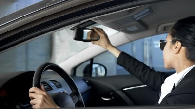 Business lady looking in rear-view mirror, driving automobile, traffic rules